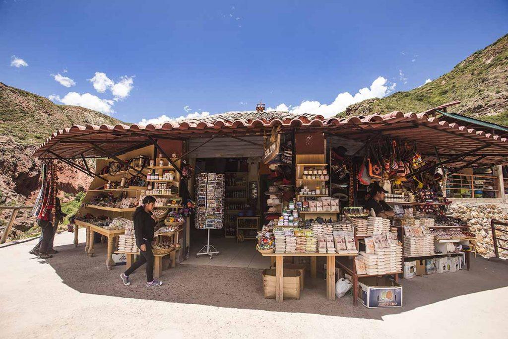 A woman walks past a souvenir shop selling all kinds of Maras salt.