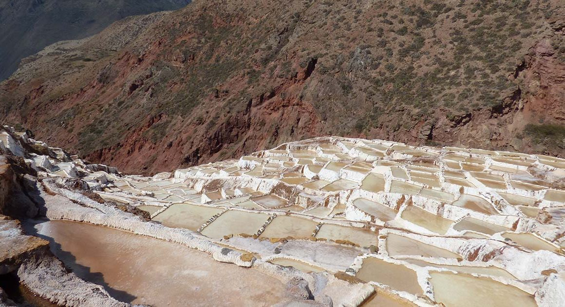The beige Maras salt ponds extend to the edge of the hill.