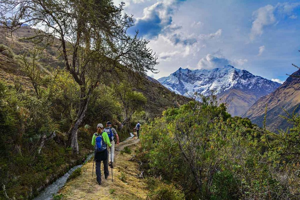 Trekkers walk a flat portion of the Salkantay trail in the direction of snow-covered mountains.