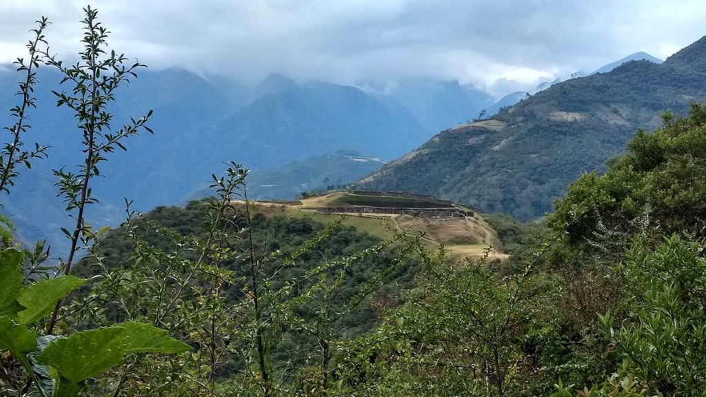 The Inca ruins Vitcos are seen at a distance through vegetation.