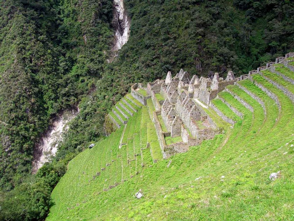 Inca terraces and remains of buildings sit on the side of a steep, grassy mountain.